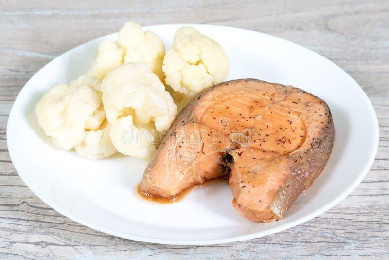 dieet voedsel Gestoomd zalmlapje vlees en coliflower op een witte plaat stock afbeelding