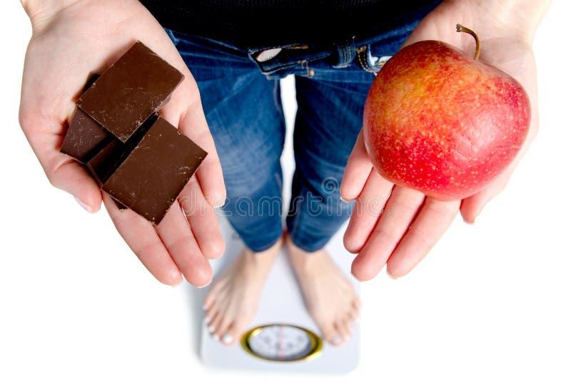 Dieet Vrouw die Lichaamsgewicht op de chocolade en de appel van de Wegende Schaalholding meten stock fotografie