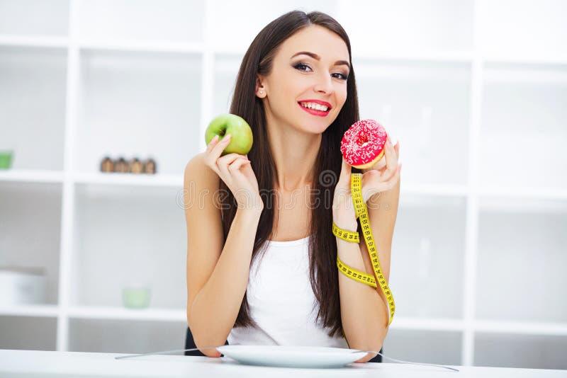 Dieet Vrouw die Lichaamsgewicht op Wegende Schaalholding Donu meten stock foto