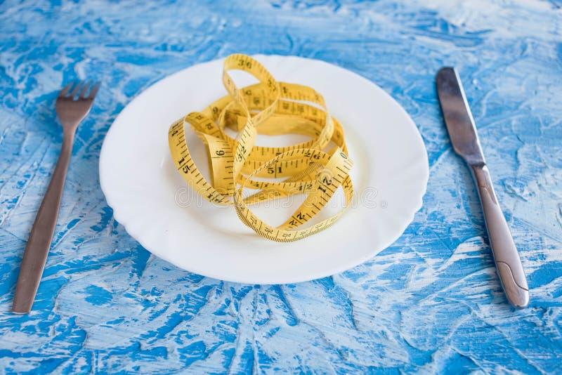 Dieetconcept die - band gele kleur in lege plaat op blauwe achtergrond meten royalty-vrije stock fotografie