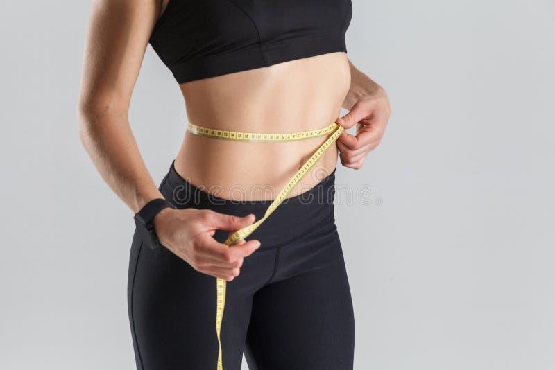 Dieetconcept, perfecte maag De centimeter van de vrouwenholding stock afbeelding