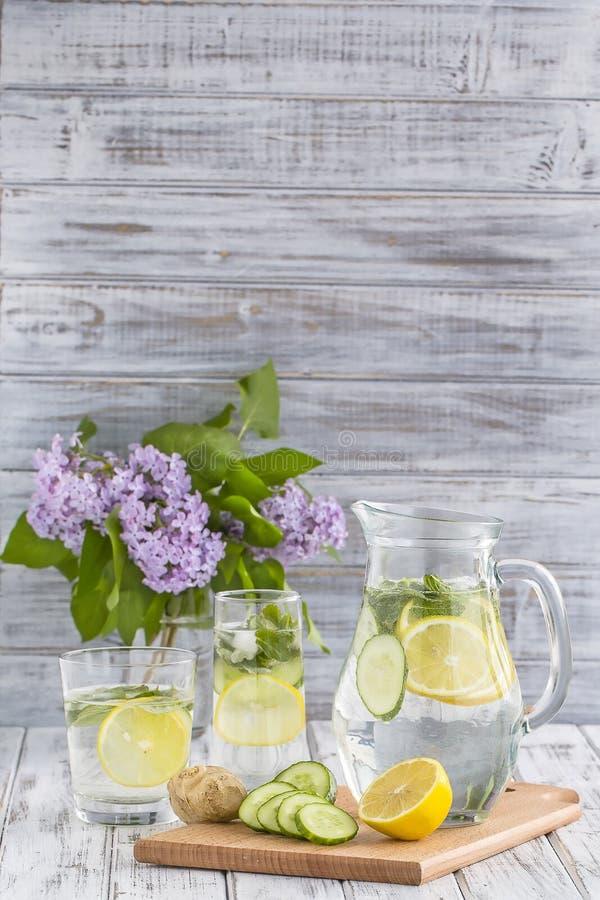 Dieetdetoxdrank met citroensap, gember, komkommer en muntbladeren in duidelijk water met ijs stock fotografie