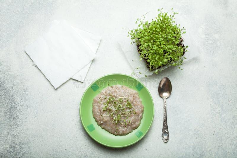 Dieetontbijt van havermeel en micro- greens op een witte achtergrond royalty-vrije stock afbeelding