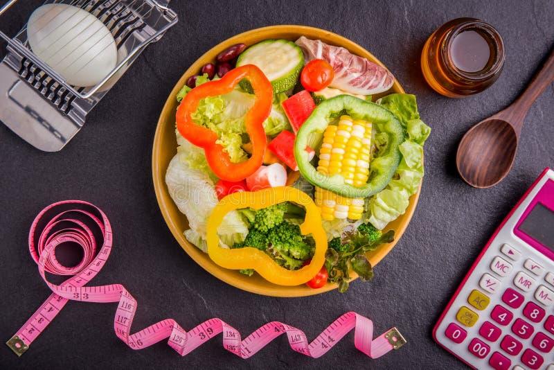 Dieetplan, meetlint, calculator voor Tellingscalorieën, salade stock fotografie