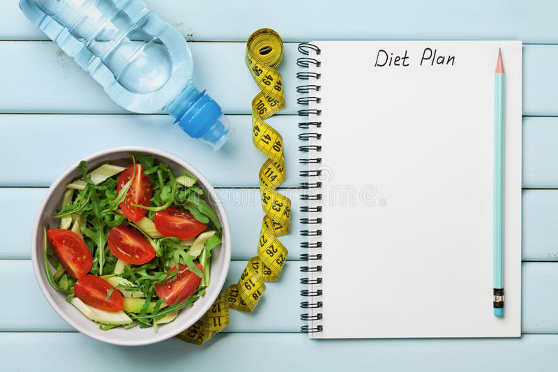 Dieetplan, menu of programma, meetlint, water en dieetvoedsel van verse salade op blauwe achtergrond, gewichtsverlies en detox co royalty-vrije stock afbeeldingen