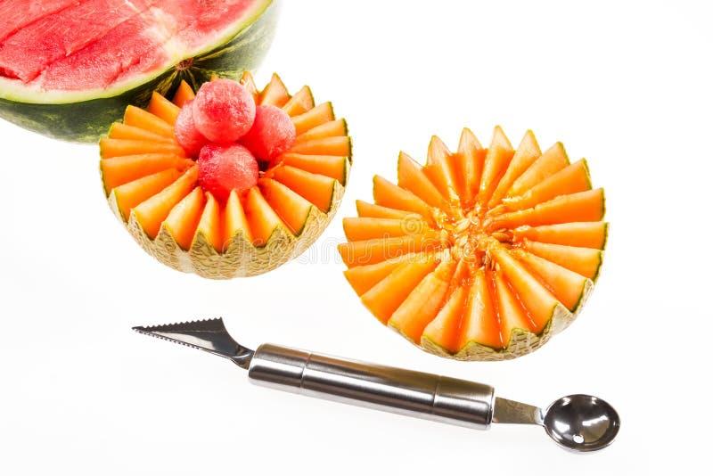 Dieetvoeding, detox Besnoeiings gele meloen en rode watermeloen naast een mes voor krullend knipsel op een witte achtergrond royalty-vrije stock foto
