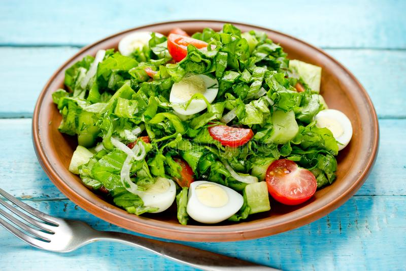Dieetvoeding groene salade met tomaten, komkommer en kwartelseieren stock foto's
