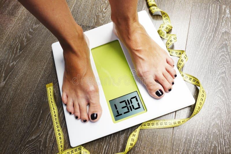 Dieetwoord op het scherm van de gewichtsschaal met vrouwenvoeten en metingsband royalty-vrije stock afbeelding