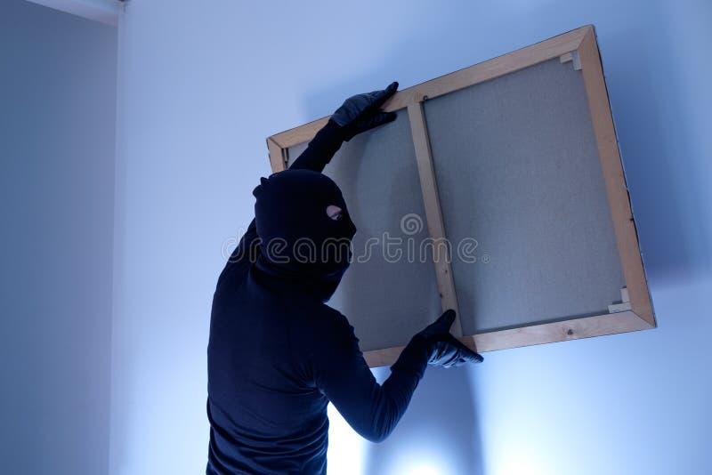 Dief die binnen huis het schilderen van de muur stelen stock foto