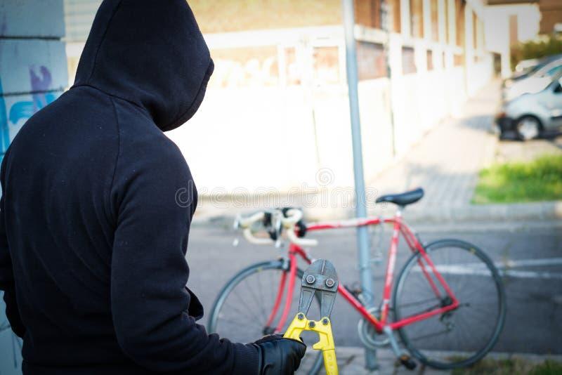 Dief die een geparkeerde fiets in stadsstraat stelen royalty-vrije stock foto