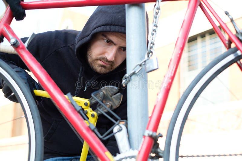 Dief die een geparkeerde fiets in stadsstraat stelen royalty-vrije stock fotografie