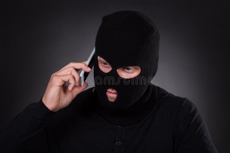 Dief die een gestolen mobiele telefoon met behulp van royalty-vrije stock fotografie