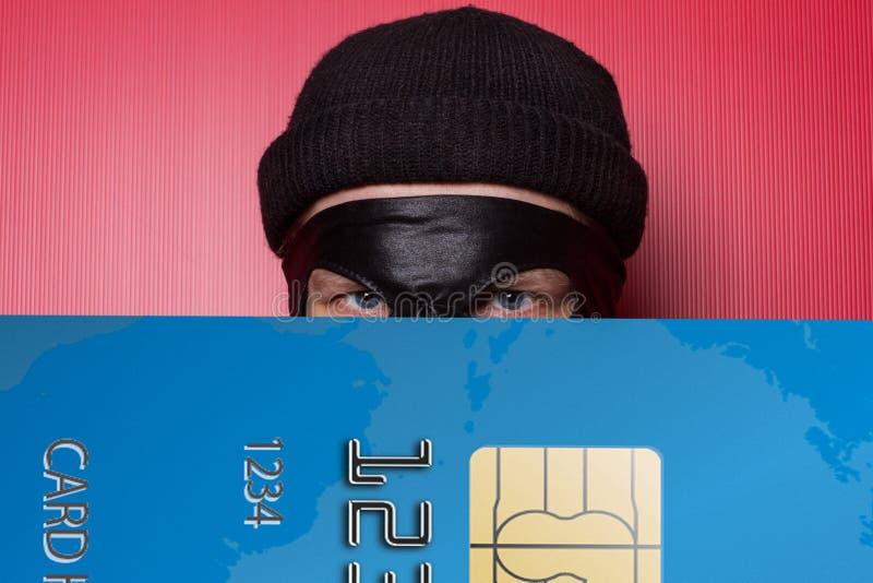 Dief die met grote blauwe creditcard glimlachen royalty-vrije stock afbeeldingen