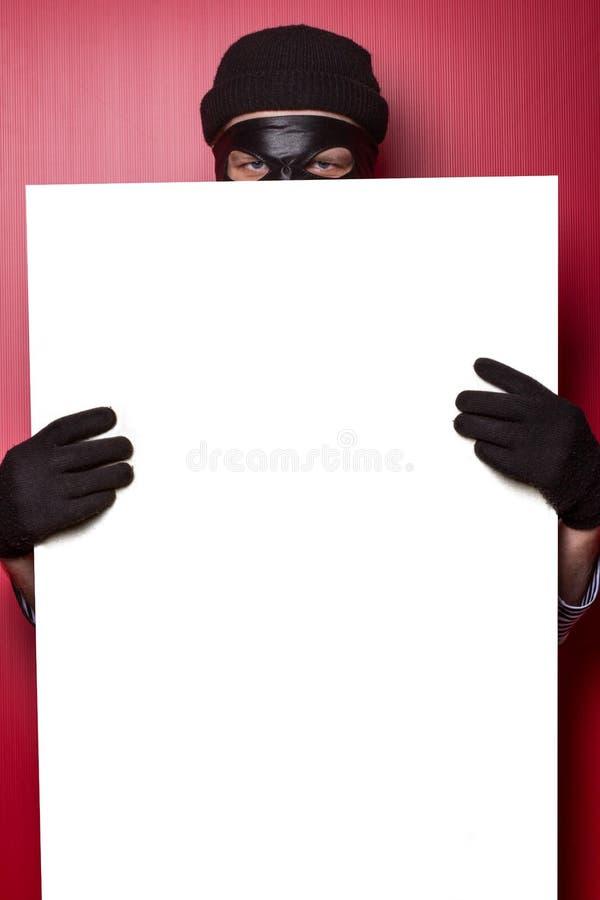 Dief het verbergen achter advertentie stock afbeeldingen