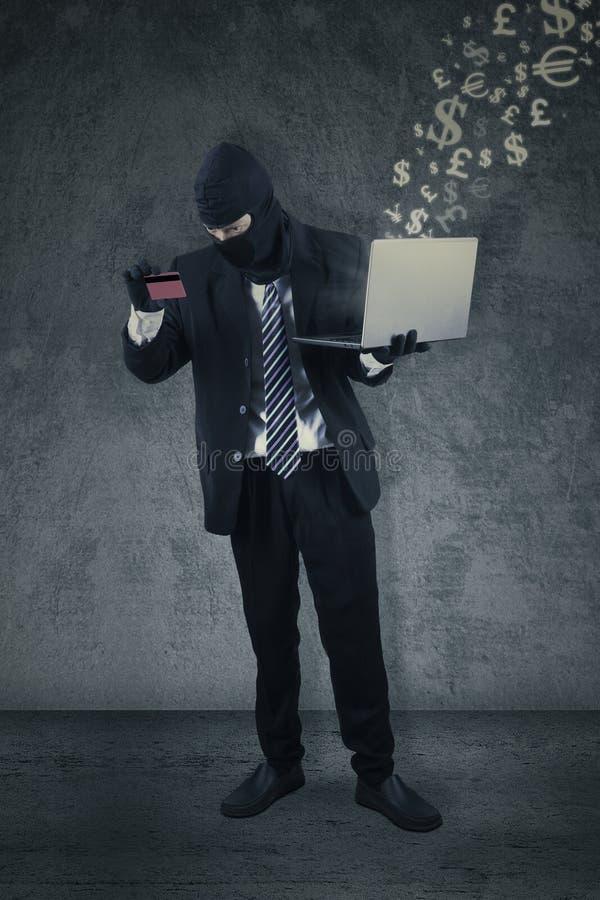 Dief met creditcard en laptop royalty-vrije stock afbeelding