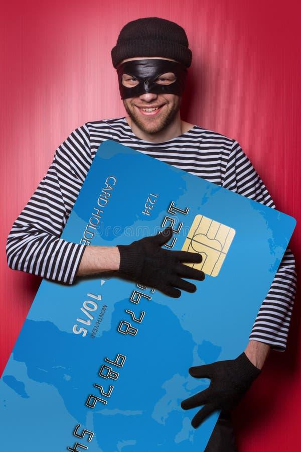 Dief met grote blauwe creditcard stock afbeelding