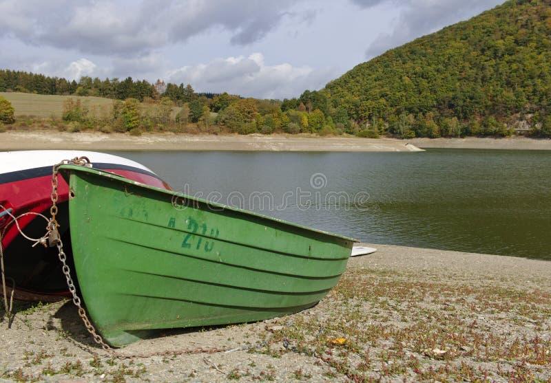 Diemelsee, riva della Germania - lago con Pebble Beach, barca verde tirata e colline boscose nella distanza immagine stock