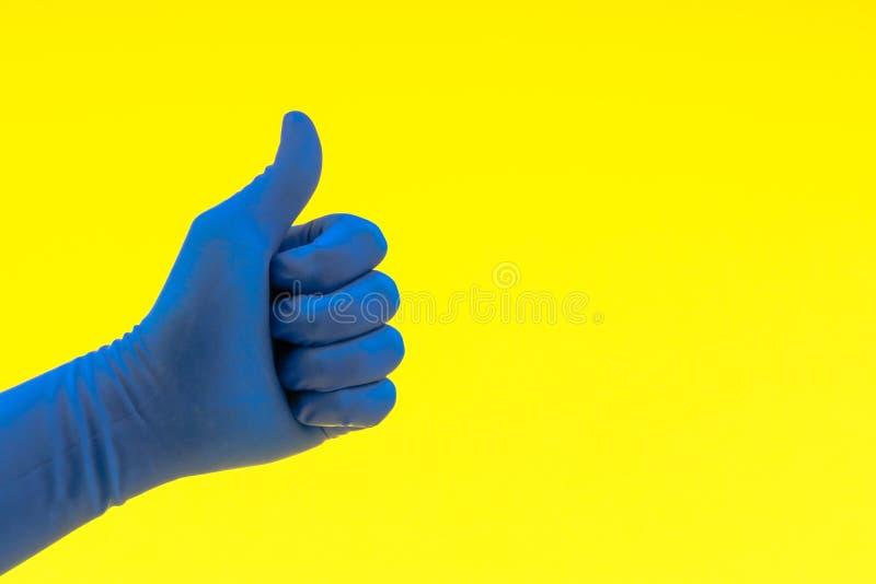 Dien een blauwe handschoen met tekenduimen omhoog of goed in stock fotografie