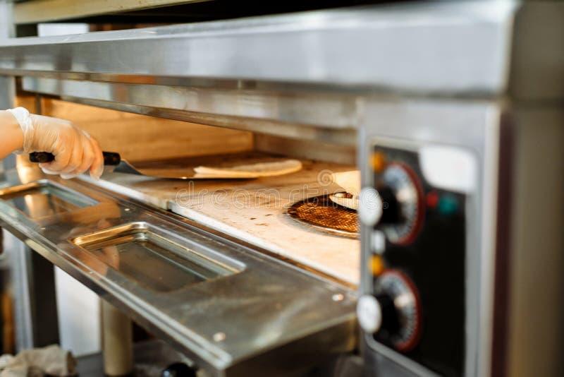 Dien een plastic handschoen in terugtrekt zich van het ovenbaksel met een metaalspatel stock afbeeldingen