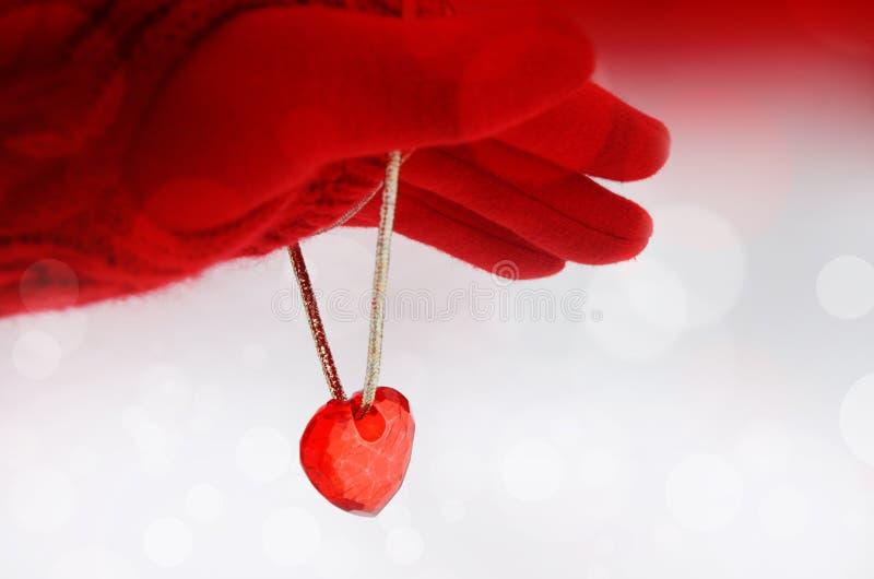 Dien een rode handschoen en een rood hart op een lichte achtergrond in beeld royalty-vrije stock fotografie