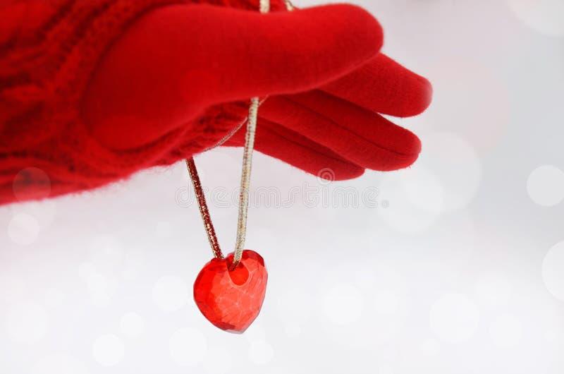 Dien een rode handschoen en een rood hart op een witte achtergrond in beeld stock foto