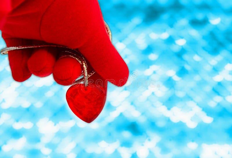 Dien een rode handschoen in houdend een hart op een abstracte blauwe achtergrond beeld stock afbeeldingen