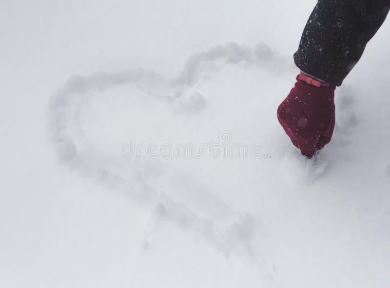 Dien een rode vuisthandschoen in trekt hart op sneeuw Hart op sneeuw royalty-vrije stock foto