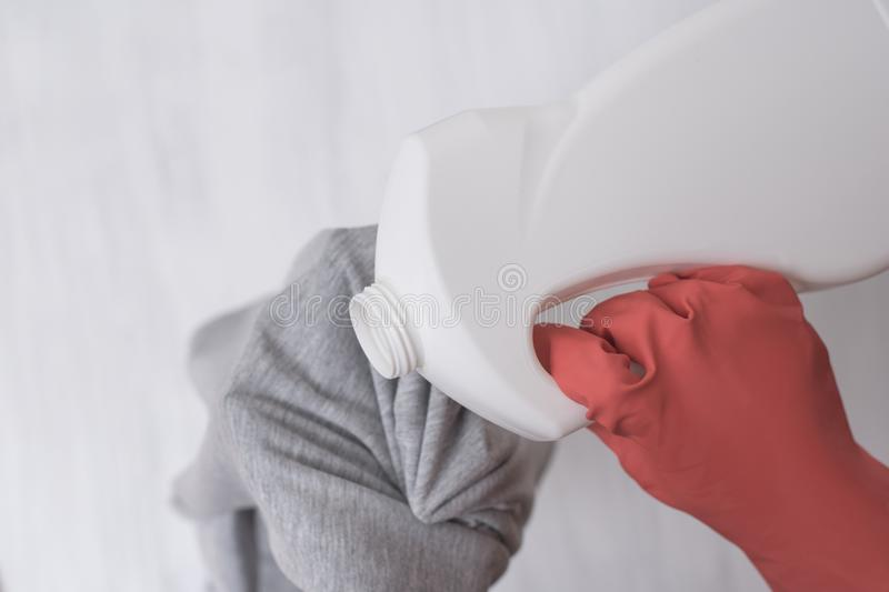 Dien handschoen in giet vloeistof voor was op kleren Close-up stock afbeeldingen