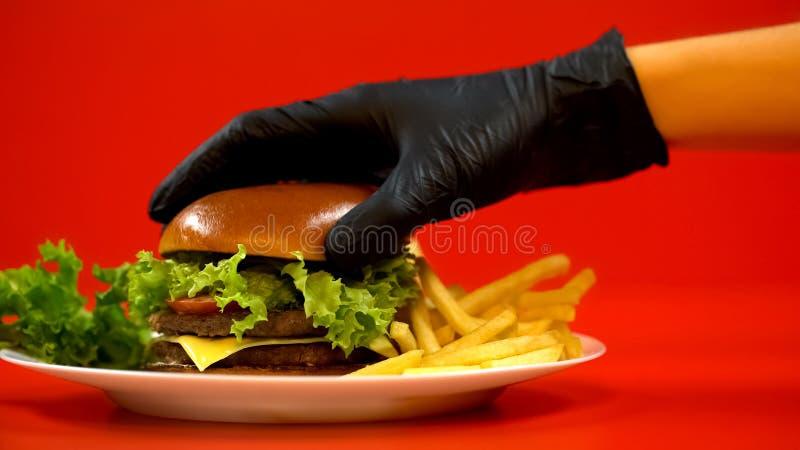 Dien handschoen in zettend broodje op hamburger, chef-kok die maaltijd voorbereiden, controlerend kwaliteit stock afbeelding