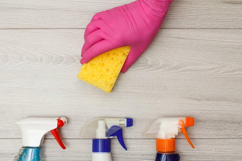 Dien rubberhandschoen in houdend synthetische sponsen met waterspuitbussen leggend op vloer stock fotografie
