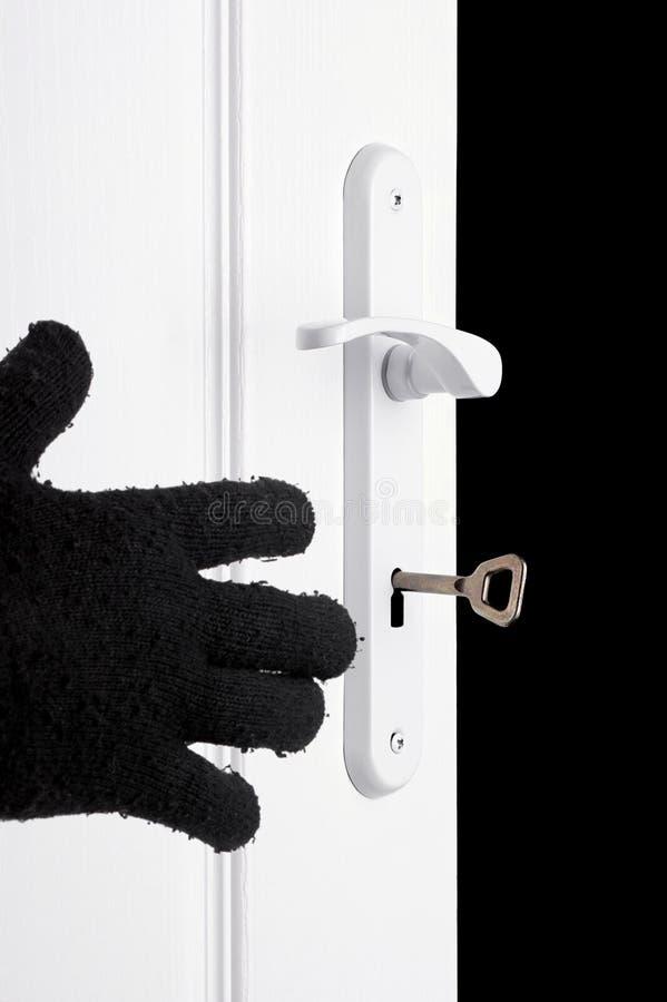 Dien zwarte handschoen bij de deur in. stock fotografie
