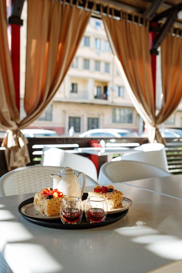 Dienblad met een theepot, koppen en cakes op een lijst in een koffie tegen het venster royalty-vrije stock fotografie