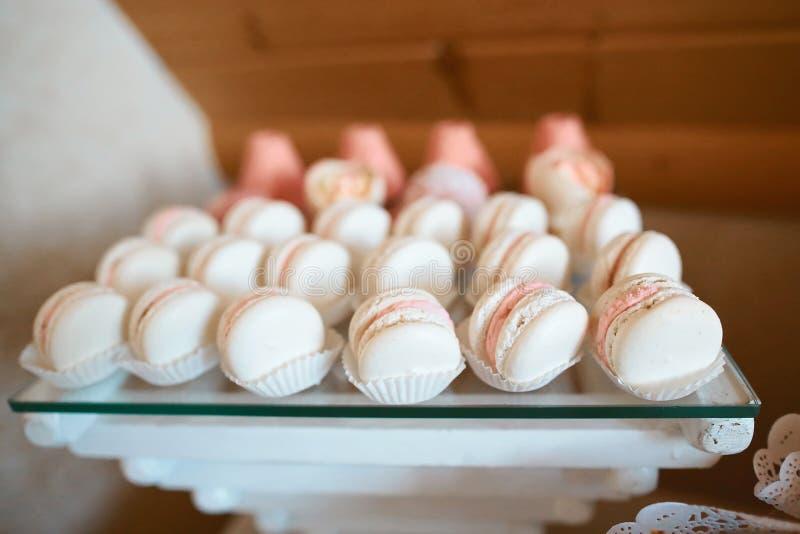 Dienblad met heerlijke cakes en makaron Kleurrijke makarons De elegante zoete lijst met grote cake, cupcakes, cake knalt op diner royalty-vrije stock afbeelding