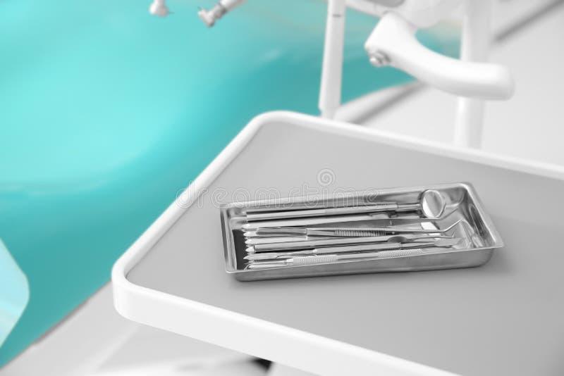 Dienblad met tandhulpmiddelen op lijst in kliniek royalty-vrije stock foto