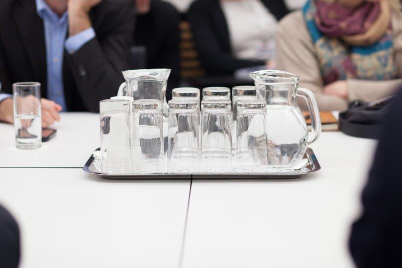 Dienblad met waterkruik en glazen water stock afbeelding