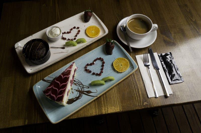dienbladtribunes op gesneden chocoladecake en drank stock fotografie