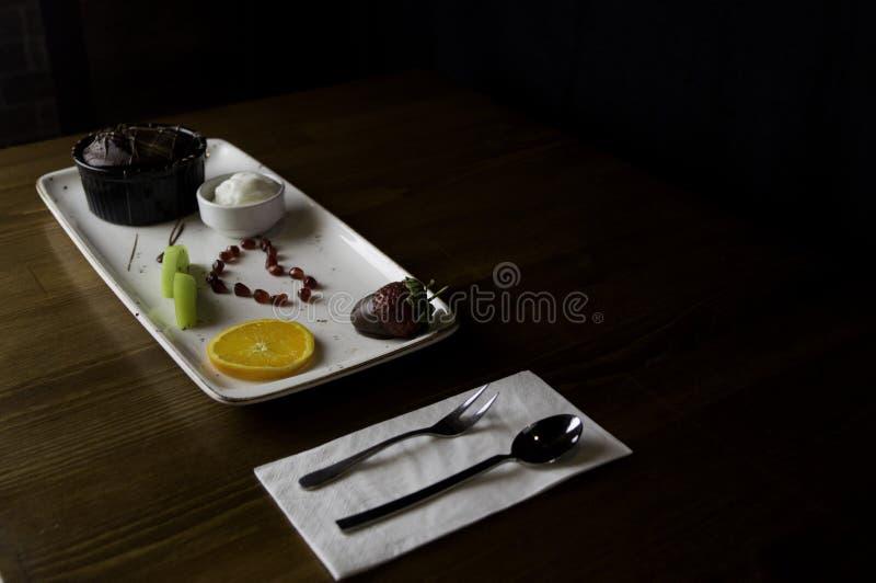 dienbladtribunes op gesneden chocoladecake en sinaasappel royalty-vrije stock afbeeldingen