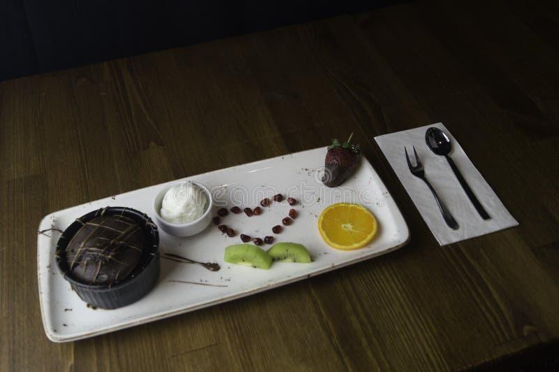 dienbladtribunes op gesneden chocoladecake en sinaasappel stock afbeelding