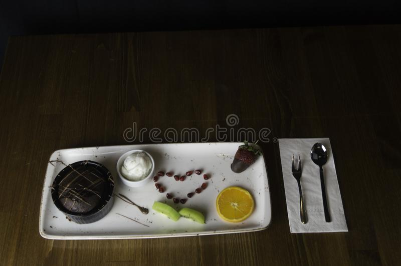 dienbladtribunes op gesneden chocoladecake en sinaasappel stock foto's