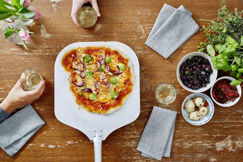 Dienende köstliche organische Pizza zu den Freunden heiß aus dem Ofen heraus lizenzfreie stockbilder