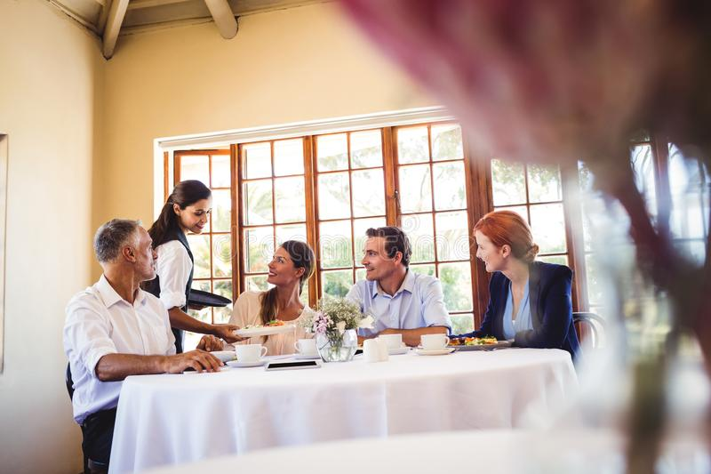Dienende Nahrung der Kellnerin auf dem Tisch stockbild