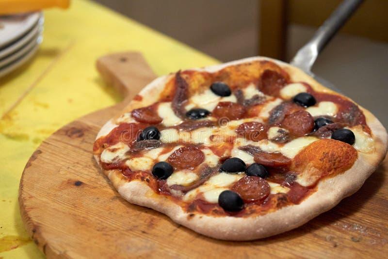 Dienende Pizza auf einem Schneidebrett stockbilder