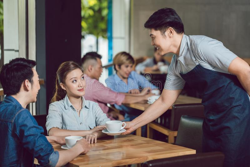 Dienender Kaffee des Kellners zur jungen Frau im Café lizenzfreies stockfoto