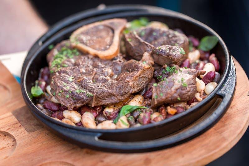 Dienendes gegrilltes Rindfleischsteak mit Bohnennahaufnahme auf einer Platte auf einer Tabelle stockfotos