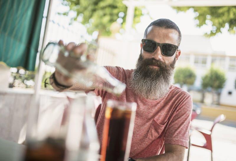 Dienendes Kokssoda des bärtigen Mannes auf whishky Getränk in der Freienbarterrasse stockbild