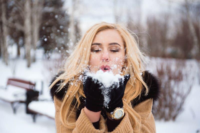 Dient de vrouwen blazende sneeuw binnen langzame motie in royalty-vrije stock afbeeldingen