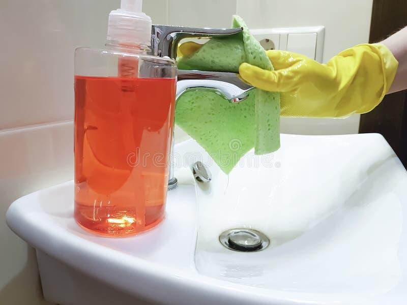 Dient gele handschoenen in wassen het huishouden van het gootsteenhuishouden royalty-vrije stock foto