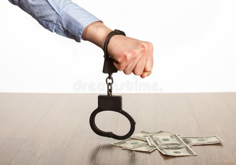 Dient handcuffs en geld op de lijst in stock afbeelding