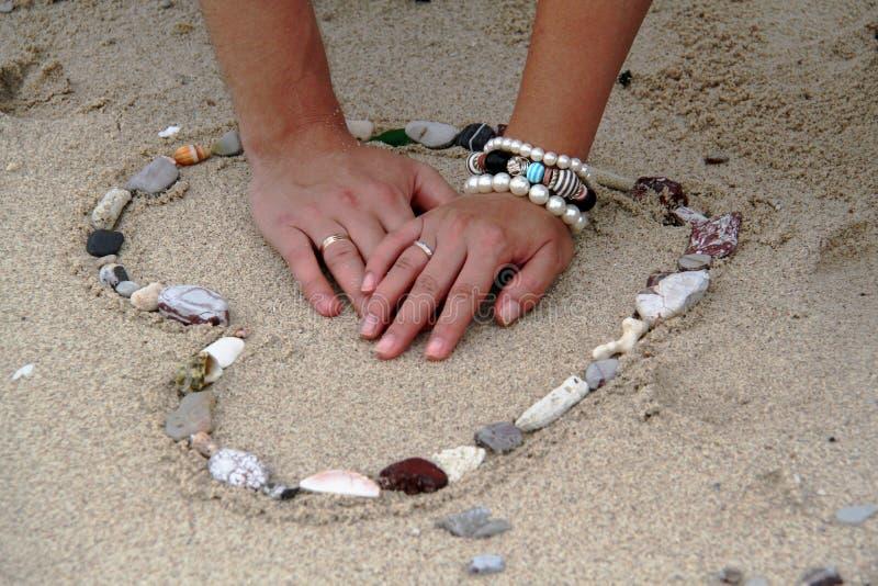 Dient het hart in het zand in stock afbeelding