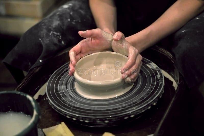 Dient klei in vormen het product op een wiel van de pottenbakker, close-up stock afbeeldingen